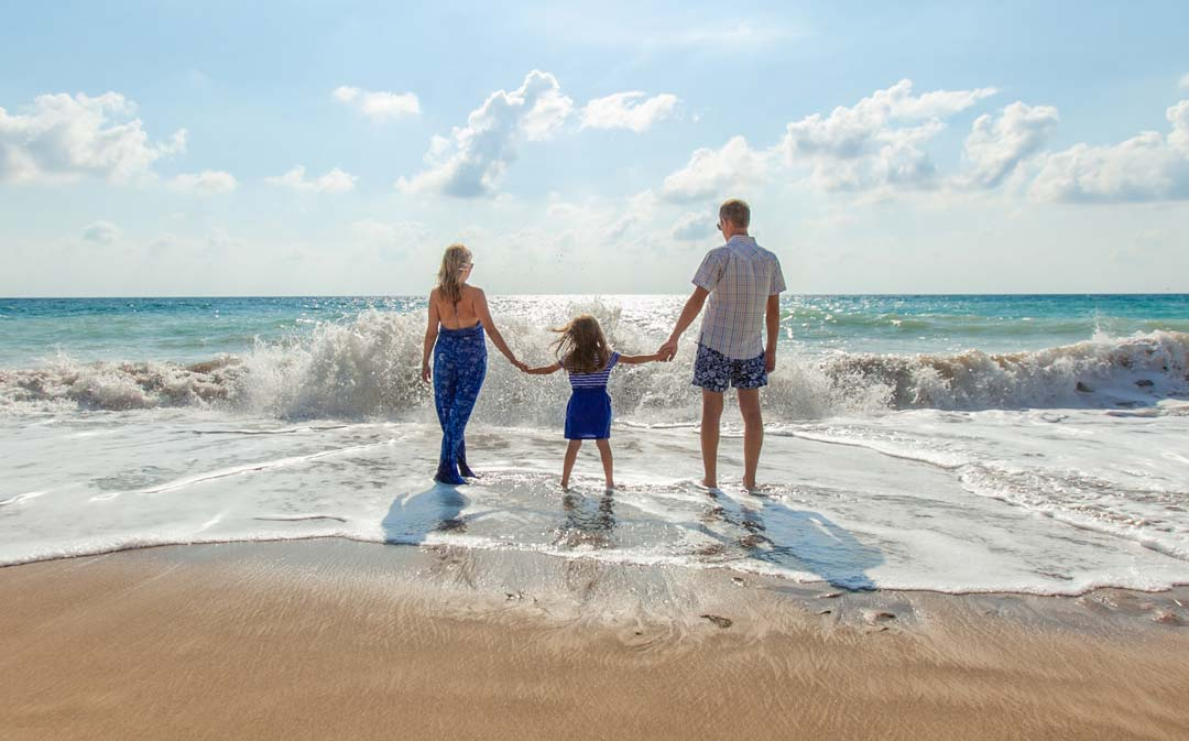 Family standing in water at beach. Universal life insurance for family at the beach